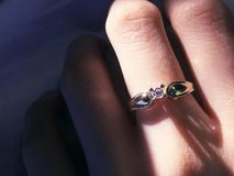 关闭在手指的典雅的钻戒有灰色围巾背景 钻戒 库存图片