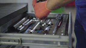 关闭技工的手手套的采取工具在箱子外面并且一起收集零件 工作者定象汽车 股票视频