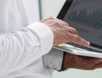 关闭 商人使用一台膝上型计算机与财务数据一起使用 免版税库存图片