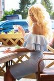 典雅的蓝色礼服的秀丽肉欲的妇女在咖啡馆 图库摄影