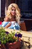 典雅的蓝色礼服的秀丽肉欲的妇女在咖啡馆 免版税库存照片