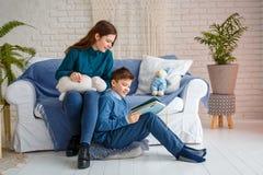 兄弟和姐妹读一本书 免版税库存照片