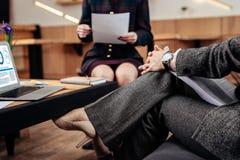 兴旺的女实业家佩带的手手表谈话与秘书 免版税库存图片