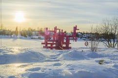 剧烈的snowscape在有桃红色木architechture的一条冻在森林之外的河和房子 免版税库存图片