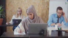 回教妇女在办公室在纸在屏幕工作,做笔记并且看 股票视频