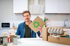 回收符号 拿着纸板与的年轻负责任的人回收象,当坐在与其他废物的桌上在时 免版税库存照片