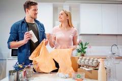 回收 投入空的塑料和纸的负责任的年轻夫妇在垃圾袋,当看彼此在附近时 免版税库存图片