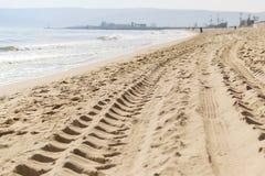 Ślada samochodowe opony na piasku morze plaża przy wody krawędzią zdjęcia stock