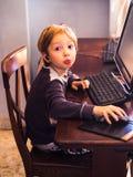 Śliczna śmieszna chłopiec przy komputerem z słuchawki zdjęcia stock