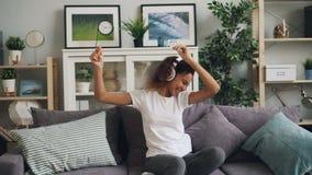 Śliczna amerykanin afrykańskiego pochodzenia dziewczyna słucha muzyka używać hełmofony, śpiew i dancingowego obsiadanie na leżanc zbiory wideo