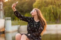 Śliczna brunetki dziewczyna robi selfie portretowi w parku blisko wody fotografia stock