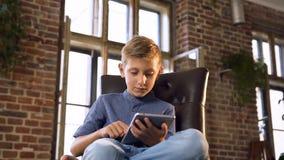 Śliczna caucasian chłopiec używa pastylka komputer Młoda nastolatek chłopiec bawić się gry na cyfrowej pastylce _ Pojęcie zbiory