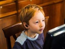 Śliczna chłopiec bawić się przy komputerem osobistym koncentrującym obrazy royalty free