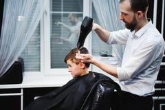 Śliczna chłopiec dostaje ostrzyżenie fryzjerem przy zakładem fryzjerskim zdjęcie stock