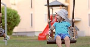 Śliczna chłopiec jazda na huśtawce w boisku zdjęcie wideo