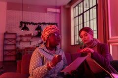 Śliczna długowłosa młoda kobieta dyskutuje horoskop z kabalistą z długimi kolczykami obraz royalty free
