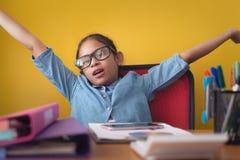 Śliczna dziewczyna podnosi ręki w górę podczas gdy ono uśmiecha się z szczęściem odizolowywającym na żółtym tle obraz stock