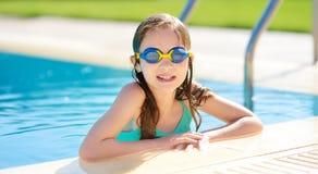 Śliczna młoda dziewczyna jest ubranym pływackich gogle ma zabawę w plenerowym basenie dziecka uczenie pływanie Dzieciak ma zabawę obraz royalty free