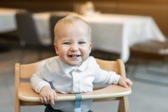 Śliczna mała chłopiec w białym polo koszulki obsiadaniu w drewnianym dziecka krześle i śmiać się przy kawiarnią indoors Portret fotografia royalty free