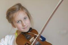 Śliczna mała dziewczynka w pięknym smokingowym bawić się skrzypce Radosne i szczęśliwe emocje szkolenie Edukacja szkoła Estetyczn fotografia stock
