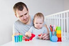 Śliczna mała preschooler dziewczyna i jej ojciec bawić się z plasteliną fotografia royalty free