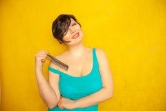Śliczna szczęśliwa uśmiechnięta dziewczyna z krótkim czarni włosy z uderzeniami zabawę z gręplą na żółtym stałym Pracownianym tle fotografia stock