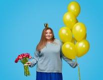 Śliczna tłuściuchna kobieta z balonami i bukietem zdjęcie stock
