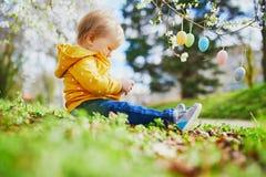 Śliczna trochę jeden roczniak dziewczyna bawić się jajecznego polowanie na wielkanocy zdjęcie royalty free