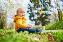 Śliczna trochę jeden roczniak dziewczyna bawić się jajecznego polowanie na wielkanocy obraz royalty free