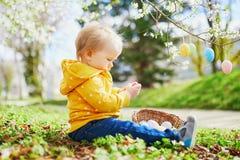 Śliczna trochę jeden roczniak dziewczyna bawić się jajecznego polowanie na wielkanocy zdjęcia royalty free