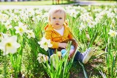 Śliczna trochę jeden roczniak dziewczyna bawić się jajecznego polowanie na wielkanocy fotografia royalty free