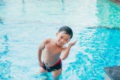 Śliczni azjatykci dzieciaka cleaning ucho po pływać w basenie zdjęcie stock