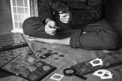 Śliczny chłopiec numizmatyk zbiera stare monety fotografia royalty free