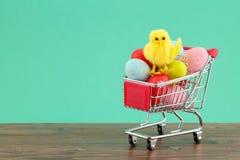 Śliczny dekoracyjny kurczak na stosie kolorowi malujący jajka w wózku na zakupy przeciw turkusowemu tłu z kopii przestrzenią obrazy royalty free