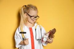 Śliczny dziecko ono wyobraża sobie jak lekarka podczas gdy bawić się z odruch lalą i młotem zdjęcia stock