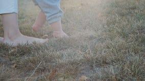 Śliczny dziecko wspiera matką podczas gdy dziecko bierze pierwszych kroki outdoors zbiory wideo