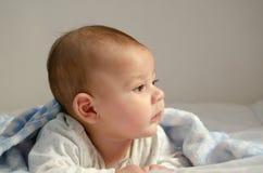 Śliczny 4 miesiąca starej chłopiec ma brzuszka czas na biel kołderce zakrywającej z błękitną koc fotografia stock