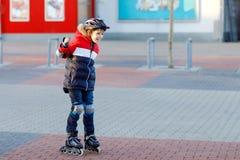 Śliczny szkolny dzieciak chłopiec łyżwiarstwo z rolownikami w mieście Szczęśliwy zdrowy dziecko w ochrony bezpieczeństwa odzieżow zdjęcia royalty free