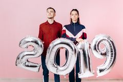Śmieszni przyjaciele dziewczyna i facet ubierający w eleganckich ubraniach trzymają balony w formie liczb 2019 na menchii zdjęcie royalty free