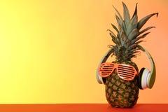 Śmieszny ananas z hełmofonami i przyjęć szkłami na koloru tle obraz royalty free