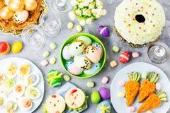 Śmieszny kolorowy Wielkanocny jedzenie dla dzieciaków z dekoracjami na stole Wielkanocny obiadowy pojęcie zdjęcie stock