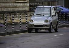 Śmieszny mały samochód parkujący w ulicie obraz royalty free