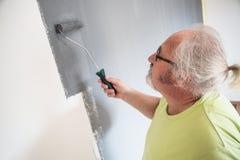 Śmieszny starszy mężczyzna maluje ścianę zdjęcia stock