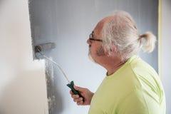 Śmieszny starszy mężczyzna maluje ścianę fotografia royalty free