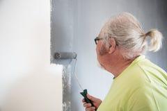 Śmieszny starszy mężczyzna maluje ścianę fotografia stock
