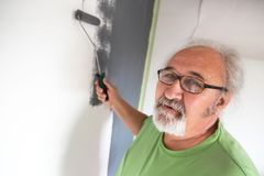 Śmieszny starszy mężczyzna maluje ścianę obrazy stock