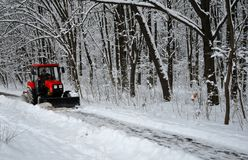 Śnieżna maszyna, czerwony ciągnik czyści śnieg od śniegu w tle las obraz royalty free