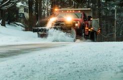Śnieżny pług przy półmrokiem utrzymuje drogi w mieszkaniowym sąsiedztwie podczas śnieżnej burzy fotografia royalty free