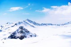 Śnieg nakrywał szczyt Elbrus wysokość pod jasnymi błękitnymi panoramicznymi niebami zdjęcie stock