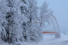 Śnieg zakrywał zawieszenie most krzyżuje rzekę wewnątrz norrthen Szwecja obrazy stock